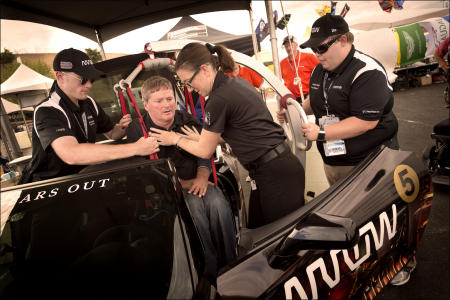 A team of engineers uses a hoist to load Sam Schmidt into the car before he heads to the track at Sonoma Raceway.
