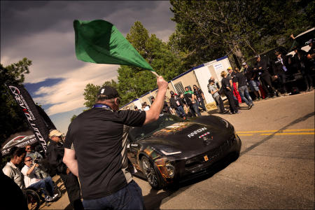 Arrow Electronics CEO Mike Long drops the green flag as the SAM car starts a run up the Pikes Peak International Hill Climb. Previously, Schmidt drove the Arrow SAM car to the Pikes Peak Summit in 15 minutes and reached a top speed of 80 mph.