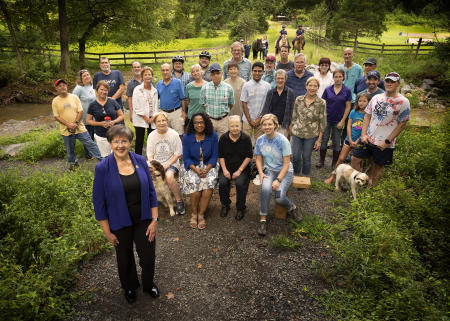 Kathy Smith and her supporters assembled in the wooded recreation area that lost a bridge that connected local communities. Without the bridge they were cut off and she was there to show her support for the repair of the bridge.